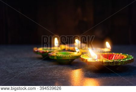 Close Up Of Clay Lit Light A Fire Already On Diya Or Oil Lamp, Studio Shot On Concrete Background, D