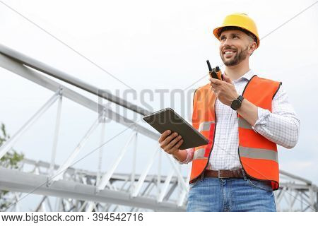 Professional Engineer With Tablet And Walkie Talkie Near High Voltage Tower Construction Outdoors. I