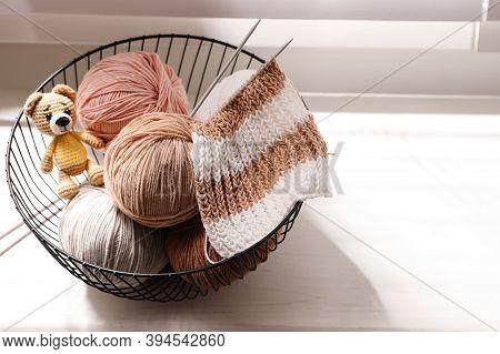 Yarn Balls, Knitting Needles And Cute Handmade Toy Bear In Metal Basket On Window Sill Indoors, Spac