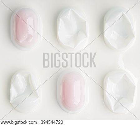 Macro Closeup  View Of Row Medical Red Round Pills Protected In Plastic Capsule On White Pharmaceuti