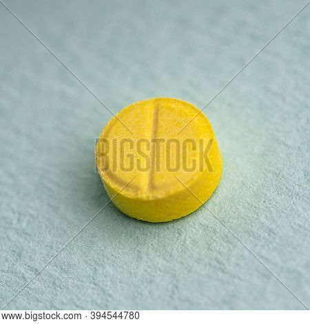 Yellow Medical Round Pill Over Light Blue Background