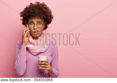 Unhappy Stressed Shocked Afro American Woman Talks Via Mobile Phone, Holds Takeout Coffee, Hears Bad