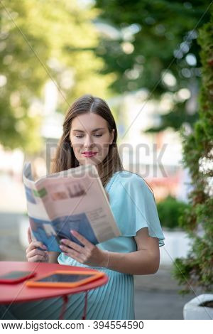 Charming Brown-haired Female Reading Sitting In Cafe, Reading Newspaper