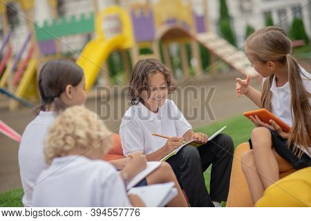 Group Of Pupils Sitting Outside And Preparing Homework