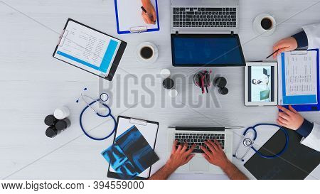 Top View Of Resident Physicians Advising With Doctor Using Videocall Sitting On Desk In Clinic With