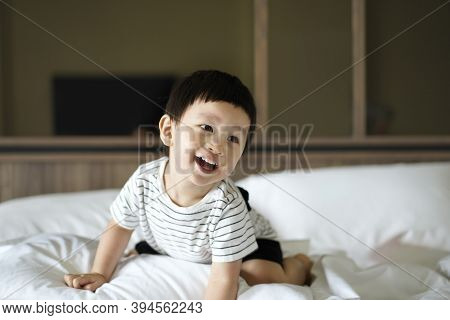 2 Years Old Little Boy Dressed In Striped Tshirt Are Relaxing And Playing In The Parent\'s Bed, Warm