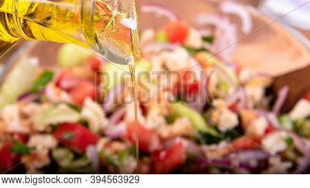 Cooking Italian Tuscan Panzanella Salad - Olive Oil Is Poured Into A Salad Of Bread, Cucumbers, Toma