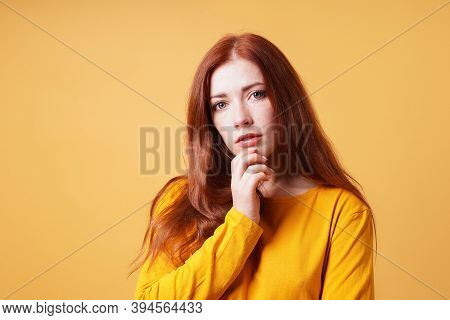 Thoughtful Young Woman With Finger On Chin Gesture - Yellow Orange Color Background With Copy Space
