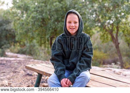 Tween Girl In A Hoodie. Portrait Of A Laughing Teenage Girl Wearing Green Hoodie Sitting On The Benc