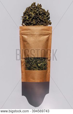 Brown Kraft Paper Pouch Bags With Tea Leaves Top View With Harsh Shadow On White Background. Coffee