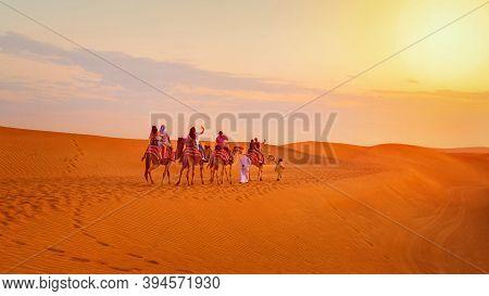 Caravan With Group Of Tourists Riding Camels Through Dubai Desert During Safari Adventure - People E