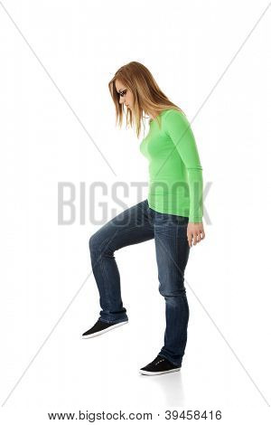 Student woman trying to trample something, isolated on white