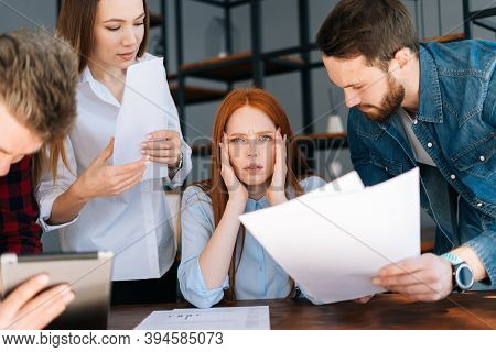 Worried F Exhausted Young Business Woman Sitting At Table, Looking At Camera, Multi-ethnic Colleague