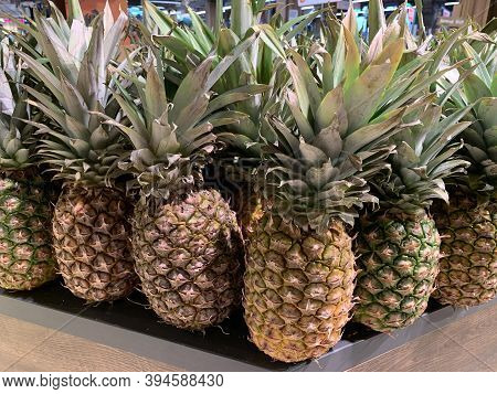 Green, Ripe Pineapples, Close-up. Exotic Fruits At The Grocery Store. Various Varieties Of Pineapple