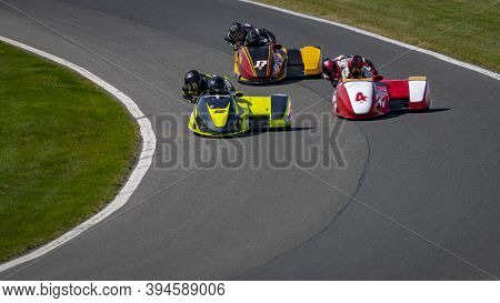 A Shot Of Several Racing Sidecars As They Corner On A Track.