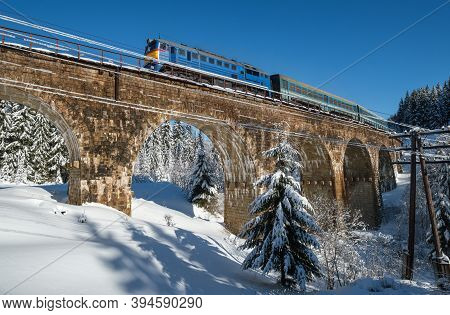 Stone Viaduct (arch Bridge) On Railway Through Mountain Snowy Fir Forest And Locomotive  With A Pass