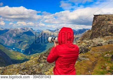 Female Tourist Taking Photo With Camera, Enjoying Geirangerfjord And Mountains Landscape From Dalsni