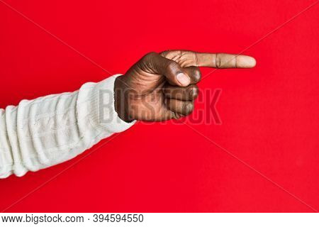 Arm and hand of african american black young man over red isolated background pointing with index finger to the side, suggesting and selecting a choice