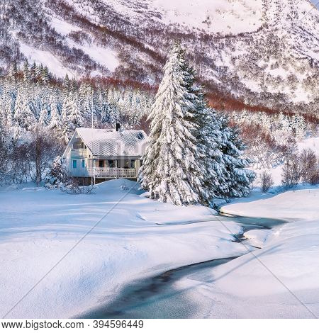 Astonishing Winter Scenery With Frozen River With Wooden Houses And Snow Covered Pine Trees Near Val