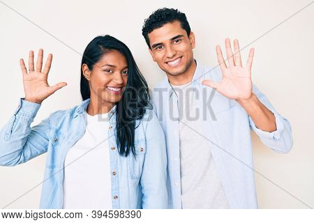 Beautiful latin young couple wearing casual clothes showing and pointing up with fingers number ten while smiling confident and happy.