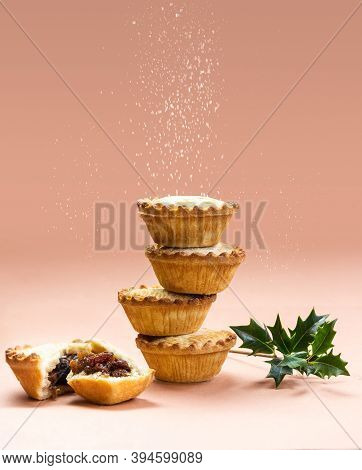 Mince Pies Stacked On Each Other On Pink Background With Sugar Sifting On Top. A Mince Pie Is A Trad