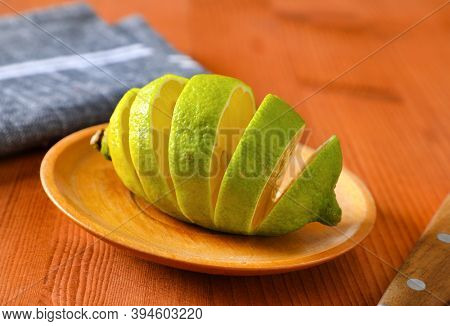 Lemon with green peel and yellow flesh, sliced on wooden plate