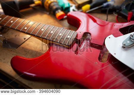 Metallic red electric guitar on guitar repair workbench or a desk,  in repair or maintenance. Pickguard detached. Double cutaway solid body guitar. Shallow depth of field.