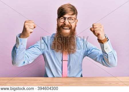 Young irish redhead man wearing business shirt and tie sitting on the table angry and mad raising fists frustrated and furious while shouting with anger. rage and aggressive concept.