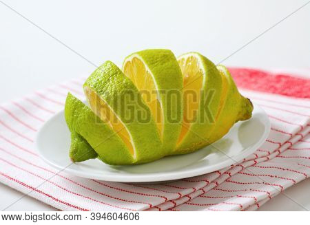 Lemon with green peel and yellow flesh, sliced on white plate