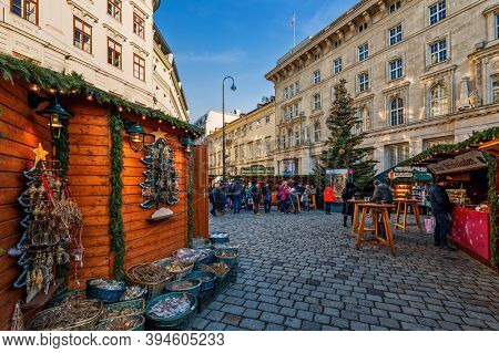 VIENNA, AUSTRIA - DECEMBER 04, 2019: People walking among wooden kiosks and stalls on selling gifts and souvenirs during famous traditional Christmas market  in old city of Vienna, Austria.