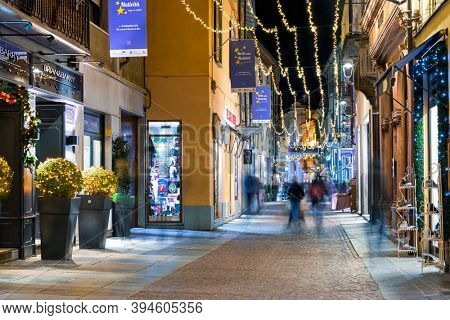 ALBA, ITALY - DECEMBER 12, 2018: People walking on the street illuminated by Christmas lights in historic part of Alba - small town famous for its white truffles in Piedmont, Northern Italy.