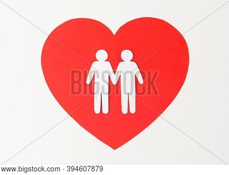 gay pride, homosexual relationship, valentines day and lgbt concept - white paper cutout of male gay couple on red heart