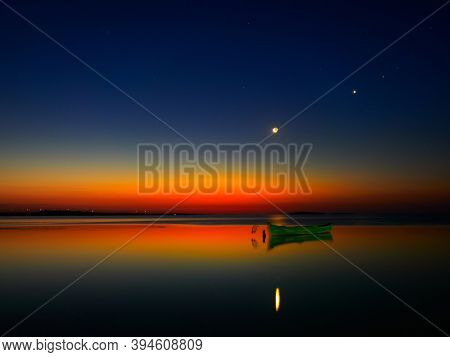 beautiful view of old fishing boat silhouette on the lake before sunrise
