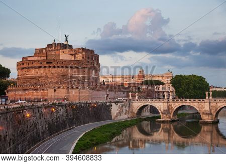 Evening view of Tiber embankment with the Mausoleum of Hadrian or Castel SantAngelo circular 2nd-century castle and Ponte Sant Angelo ancient pedestrian bridge in Rome, Italy