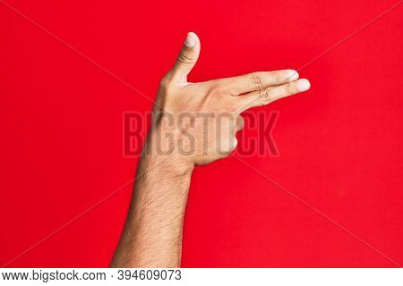 Arm of caucasian white young man over red isolated background gesturing fire gun weapon with fingers, aiming shoot symbol