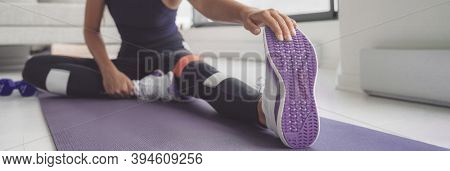 Home workout woman stretching legs on exercise mat before training. Closeup of running shoe banner panoramic. Purple shoes and floor cover.