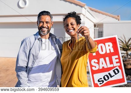 Portrait of happy mixed race couple holding house keys standing near sold signboard. Middle eastern man embracing african woman while showing house key outside of their new home. Moving home day.