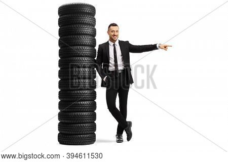 Full length portrait of a young man in a black suit leaning on a pile of car tires and pointing to the side isolated on white background