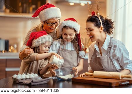 Merry Christmas and Happy Holidays. Family preparation holiday food. Grandma, mother and daughters cooking cookies.