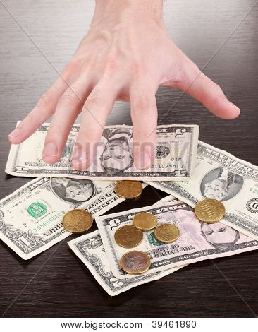 Money, which take hands on wooden table background