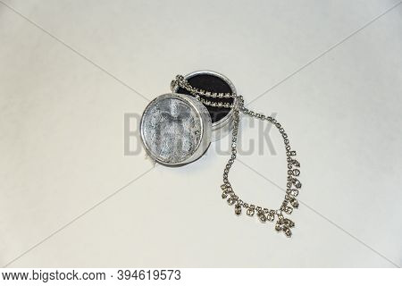 Round, Silver, Jewelry Box And Necklace Made Of Cubic Zirconia In A White Metal Frame On A White Bac