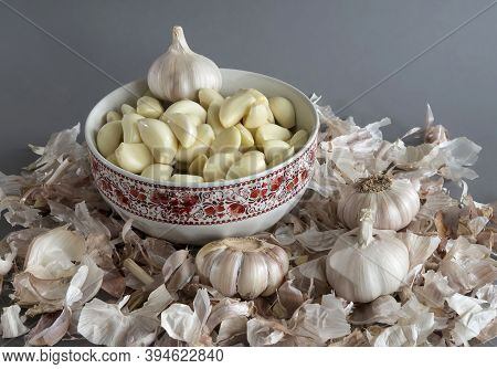 Garlic Is In The Plate. The Husk From The Garlic On Grey Isolated Background
