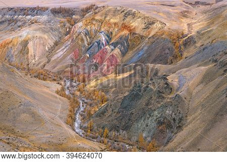 Colorful Autumn Top View Of Multi-colored Mountains With Cracks And Rifts, Meandering River And Gold