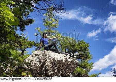 A Chinese Woman Sitting On A Rocky Outcropping Covered In Lichen On Top Of Monument Mountain In Grea