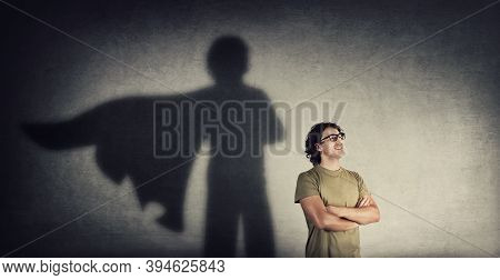 Confident Young Man Keeps Arms Crossed Smiling Optimistic As Casting A Superhero With Cape Shadow On
