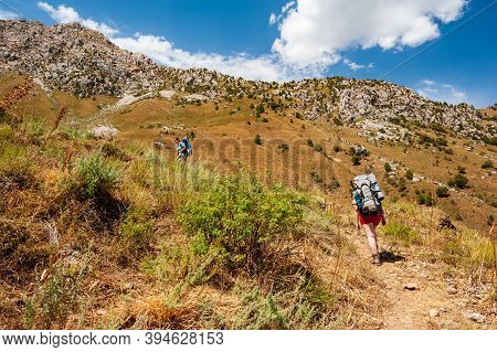 Group Of Young Hikers Trekking In Mountains. Two Women Two Men Backpacking In Summer Near Sary Chele