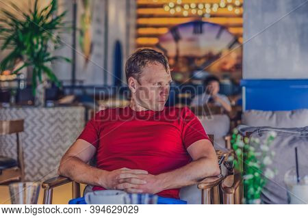 Serious Blond Man In Casual Style Red Shirt Sit In Modern Cafe, Nervous Waiting Someone Or Changes,
