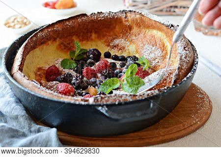 Fresh Homemade Dutch Baby Pancake With Powdered Sugar, Fresh Berries And Mint For Breakfast With A G