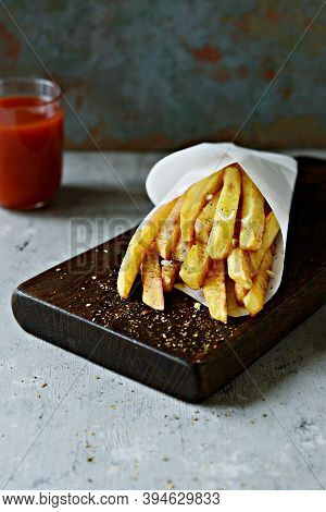 Potato Food . Baked Potatoes With Spices And Salt. Tasty French Fries On Cutting Board With Ketchup