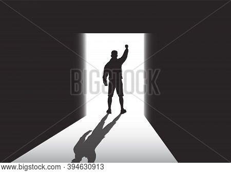 Silhouette Of Man Standing At The Door In The Dark Room With Fist Raised Up Facing The Light, Succes